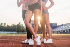 Belles jambes de trois femmes convenables d'athlète au stade Images stock