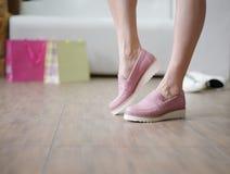 Belles jambes du ` s de femme portant les bottes roses saisonnières sur un fond de magasin Chaussures des achats de fille de mode Images libres de droits