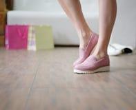 Belles jambes du ` s de femme portant les bottes roses saisonnières sur un fond de magasin Chaussures des achats de fille de mode Photo stock