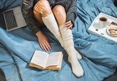 Belles jambes en gros plan dans le lit, fille avec une tasse de thé et de lire un livre photos stock