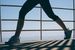 Belles jambes minces d'une jeune femme sportive dans l'espadrille bleue Images libres de droits