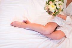 Belles jambes nues de la jeune mariée se trouvant sur le lit Jeune mariée montrant les jambes sexy sur le lit Photo libre de droits