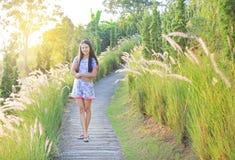 Belles jeunes femmes asiatiques détendant avec le champ d'herbe sauvage au coucher du soleil photographie stock