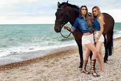 Belles jeunes femmes avec de longs cheveux posant avec le cheval noir Photographie stock