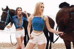 Belles jeunes femmes avec de longs cheveux posant avec le cheval noir Photos stock