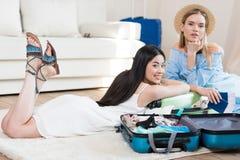 Belles jeunes femmes avec des passeports et billets emballant des valises Images libres de droits