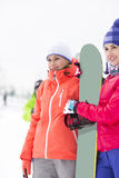 Belles jeunes femmes avec le surf des neiges regardant loin Photos libres de droits