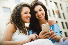 Belles jeunes femmes ayant l'amusement avec des smartphones dans la rue Photo libre de droits