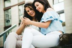 Belles jeunes femmes ayant l'amusement avec des smartphones dans la rue Image libre de droits
