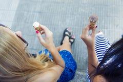 Belles jeunes femmes ayant l'amusement avec la crème glacée au parc Image libre de droits