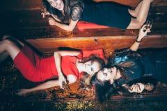 Belles jeunes femmes ayant l'amusement sur la partie folle se trouvant sur le flo photo stock