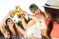 Belles jeunes femmes buvant de la bière et appréciant le jour d'été Image libre de droits