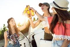 Belles jeunes femmes buvant de la bière et appréciant le jour d'été Photos libres de droits