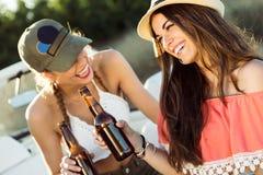 Belles jeunes femmes buvant de la bière et appréciant le jour d'été Photo libre de droits