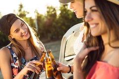 Belles jeunes femmes buvant de la bière et appréciant le jour d'été Photos stock