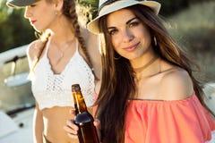 Belles jeunes femmes buvant de la bière et appréciant le jour d'été Photo stock