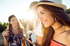 Belles jeunes femmes buvant de la bière et appréciant le jour d'été Photographie stock