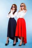 Belles jeunes femmes dans longues jupes et lunettes de soleil Image stock