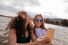 Belles jeunes femmes prenant le selfie par le lac Images libres de droits