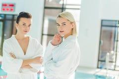 belles jeunes femmes se tenant devant la piscine au centre et au regard de station thermale Images libres de droits