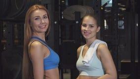 Belles jeunes femmes sportives souriant à l'appareil-photo posant au gymnase images stock