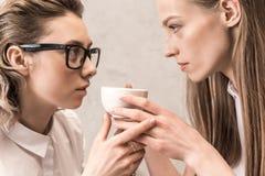 Belles jeunes femmes tenant la tasse de café et regardant l'un l'autre Photographie stock