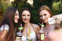 Belles jeunes filles dans des robes buvant du jus dans le jardin Photos stock