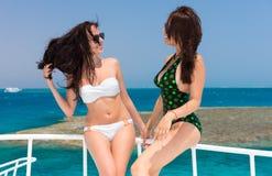 Belles jeunes filles dans le maillot de bain se tenant sur le yacht à un soleil Photos libres de droits