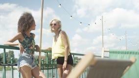 Belles jeunes filles de métis parlant près du lac et appréciant des vacances Image stock