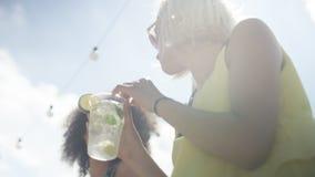 Belles jeunes filles de métis parlant près du lac et appréciant des vacances Photographie stock