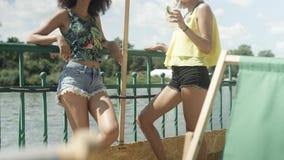 Belles jeunes filles de métis parlant près du lac et appréciant des vacances Photographie stock libre de droits