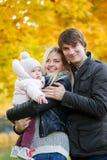 Belles jeunes paires avec la fille sur le fond de la forêt d'automne Images libres de droits