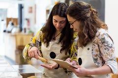 Belles jeunes vendeuses faisant l'inventaire dans le magasin organique Photo stock