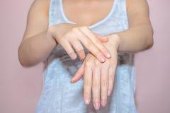 Belles mains de femme appliquant la crème Photos libres de droits