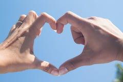 Belles mains de forme d'amour - coeur sur le ciel bleu Photographie stock