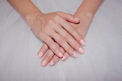 Belles mains du ` s de jeune mariée avec un clou doux Photos stock