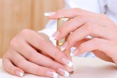 Belles mains femelles avec l'émail de bouteille de fixation Photographie stock libre de droits