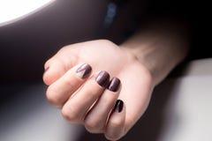 Belles mains femelles avec la manucure lumineuse Clous couverts de clou Images stock