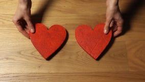 Belles mains femelles mettant deux formes rouges de coeur sur la table en bois Aimez, jour du ` s de Valentine, unité, famille, d banque de vidéos