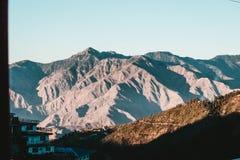 Belles montagnes et une colline avec de petites maisons images libres de droits