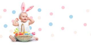 Belles oreilles de lapin de port de sourire de petite fille de Pâques, avec un panier complètement des oeufs de pâques peints col photo libre de droits
