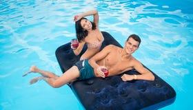 Belles paires flottant sur le matelas en piscine, cocktails potables et ayant l'amusement leurs vacances d'été Images stock