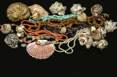 Belles perles de turquoise, corail rouge, ambre, grenat, agate colorée, perles avec des coquillages sur un fond noir photo libre de droits