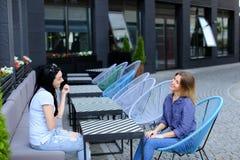 Belles personnes féminines s'asseyant au café de rue dehors Photographie stock libre de droits
