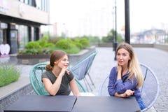 Belles personnes féminines s'asseyant au café de rue dehors Images libres de droits