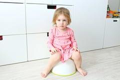 Belles petites 2 années de fille s'asseyant sur le pot Images libres de droits