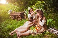 Belles petites filles dans une robe blanche posant dans l'herbe Lumière de coucher du soleil Images libres de droits