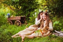 Belles petites filles dans une robe blanche posant dans l'herbe Lumière de coucher du soleil Photo stock
