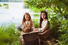 Belles petites filles dans une robe blanche posant dans l'herbe Lumière de coucher du soleil Images stock