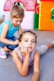 Belles petites filles se trouvant sur l'étage de cour de jeu Images stock